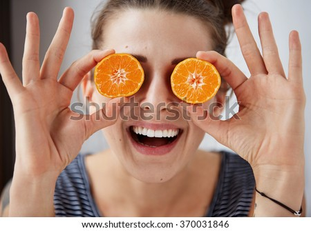 Young brunette woman holding tangerines instead of eyes, laughs and enjoys life. Harsh processing to emphasize the face structure. Human face expression body language reaction - stock photo