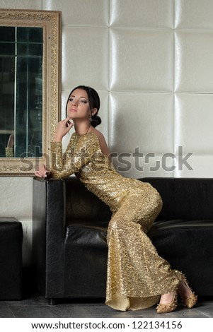 young brunette woman in gold dress on sofa