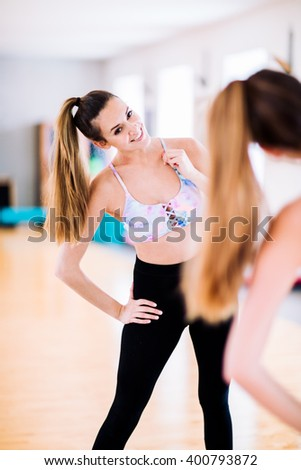 Young brunette woman in her 20s getting ready for fitness training at gym - stock photo