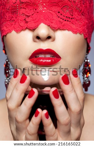 Young brunette woman in red ribbon and glass of wineposing on gray background - stock photo