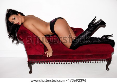 Young brunette woman in sexy black lingerie and high heel boots posing on red sofa and looking into the camera over white background
