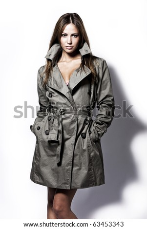 young brunette woman in topcoat studio shot on white - stock photo