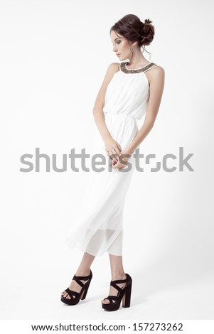 Young brunette woman in white dress. White Background. - stock photo