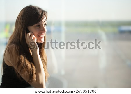 Young brunette woman is talking on mobile phone in the airport - stock photo