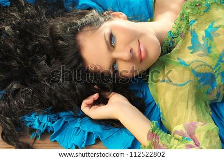 Young brunette woman lying on fabric drapery - stock photo
