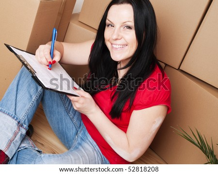 young brunette woman moving to new house - stock photo