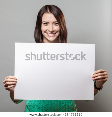young brunette woman on grey background holding blank sign - stock photo