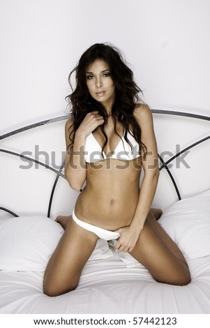 Young brunette woman on the bed - stock photo