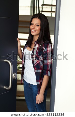 Young brunette woman opening the door of her house