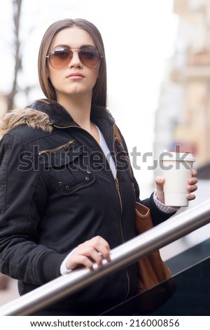 Young brunette woman outdoors with coffee. woman on street holding cup of coffee - stock photo