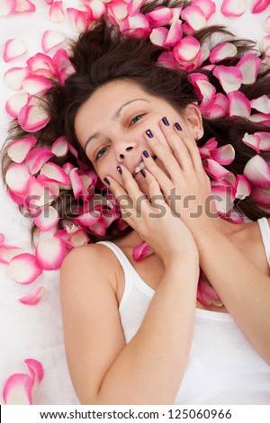 Young brunette woman relaxing on a bed with white bed covers - stock photo