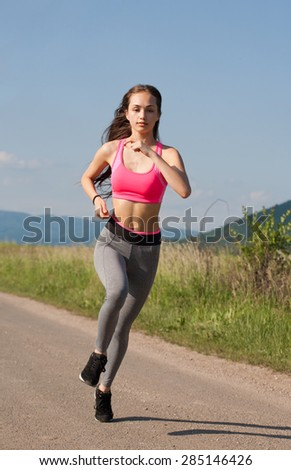 Young brunette woman running outdoors in sunny nature. - stock photo