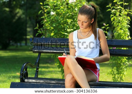 Young brunette woman studying in a park , she is sitting on a bench - stock photo