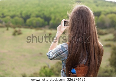 Young brunette woman using her smart phone to take home memories of hiking. - stock photo