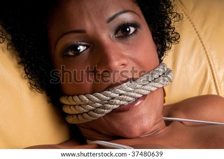 Young brunette woman very scared and bonded with ropes. - stock photo