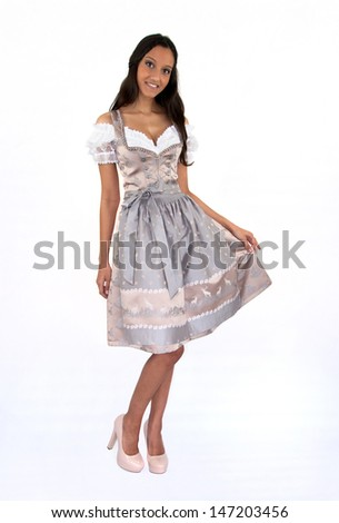 Young brunette woman wearing a dirndl posing on white background
