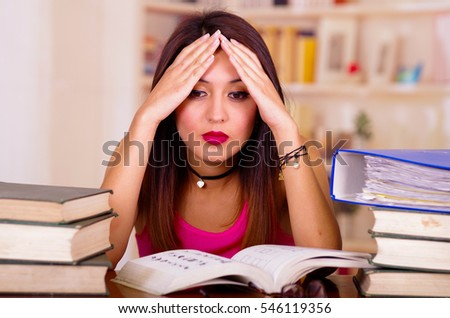 Young brunette woman wearing pink top sitting by desk with stack of books placed on it, holding hands onto head, tired facial expression and bodu language, student concept