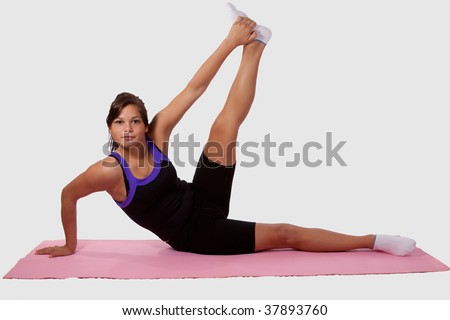 Young brunette woman wearing workout clothes doing yoga stretch lifting leg on pink mat over white - stock photo