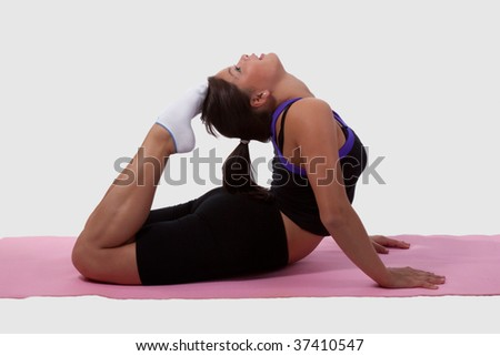 Young brunette woman wearing workout clothes doing yoga stretch on pink mat - stock photo