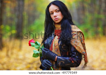 Young brunette woman with red rose portrait. Vibrant colors. - stock photo