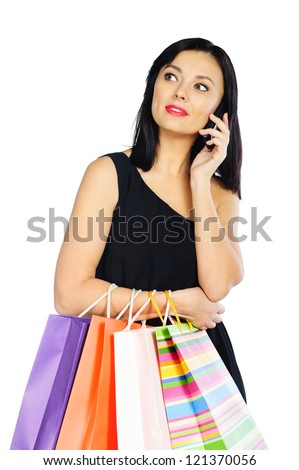 Young brunette woman with shopping bags talking via phone isolated on white background - stock photo