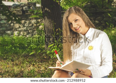 Young brunette woman writing in nature