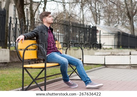 Young brutal man sitting on the bench - stock photo