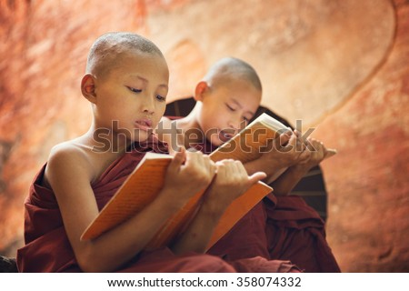 Young Buddhist novice monk reading and study outside monastery, Myanmar. - stock photo