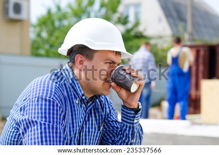 Young builder, engineer or architect taking his coffee break sipping from a plastic mug as his team continue working on site in the background - stock photo