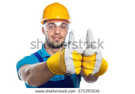 Young builder in a protective hardhat and gloves showing thumbs up 