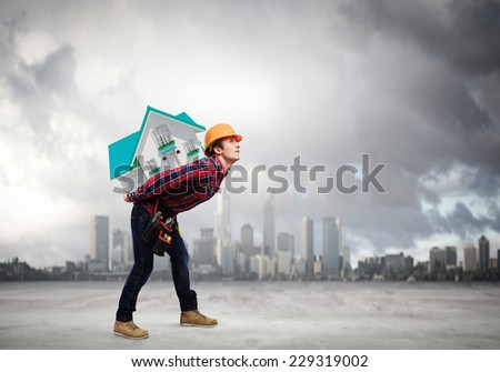 Young builder man in hardhat carrying house model on back - stock photo