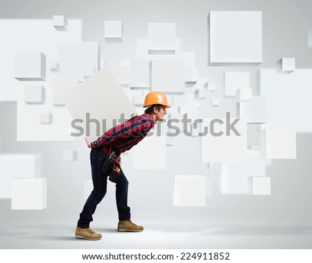 Young builder man in hardhat carrying white blank cube on back - stock photo