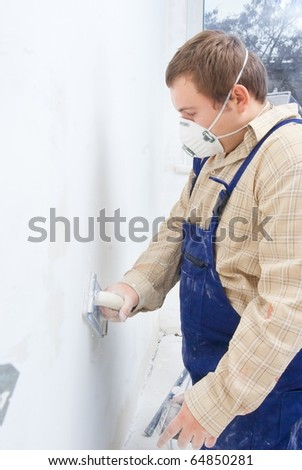 Young builder polishing the wall. house environment theme - stock photo