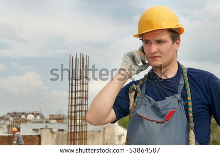 Young builder worker at construction site speaking on mobile phone