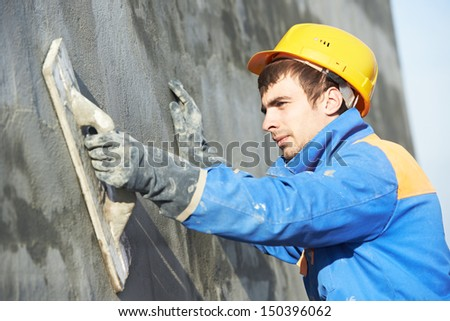 Young builder worker at facade plastering work during industrial building with putty knife float - stock photo