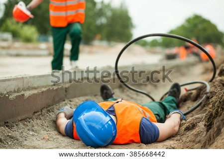 Young building worker injured at construction site - stock photo