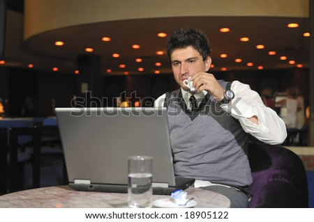 Young buisinesman drinking coffee while working on laptop - stock photo