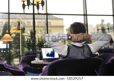 Young buisinessman sitting and working on buisiness laptop - stock photo