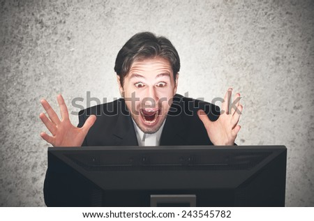 young busines man screaming at the computer, emotion, expression - stock photo