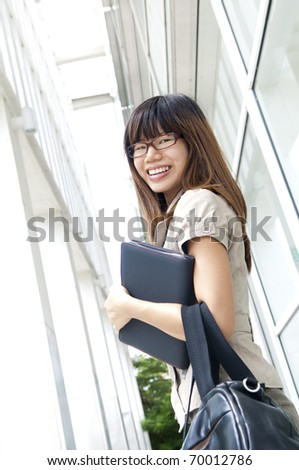 Young business businesswoman walking by an office building - stock photo