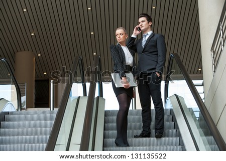 Young business colleagues going down on escalator. - stock photo