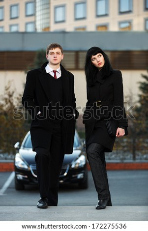 Young business couple against office building