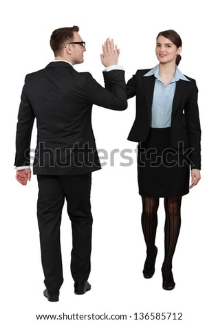 Young business couple celebrating their success giving each other a high five, against a white background.