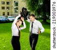 Young business couple having fun outdoor on green background - stock