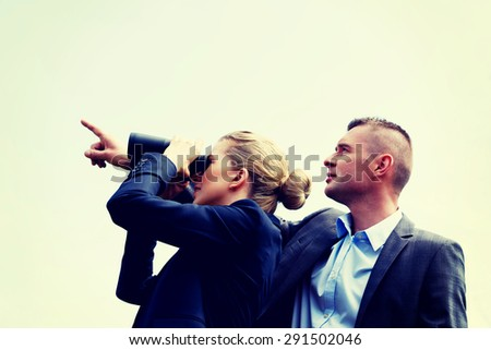 Young business couple looking at the sky - stock photo