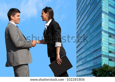 Young Business couple shaking hands over deal outdoors.