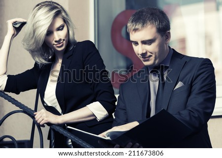 Young business couple with a folder at the office window - stock photo