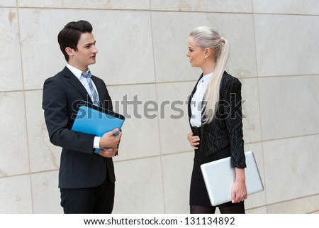 Young business couple with file and laptop having conversation.