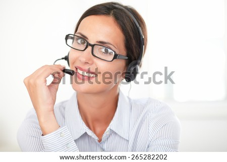 Young business employee with glasses talking on headphones while smiling and looking at you - stock photo