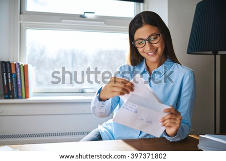 Young business entrepreneur checking her mail sitting at her desk at home with an open letter in her hand - stock photo